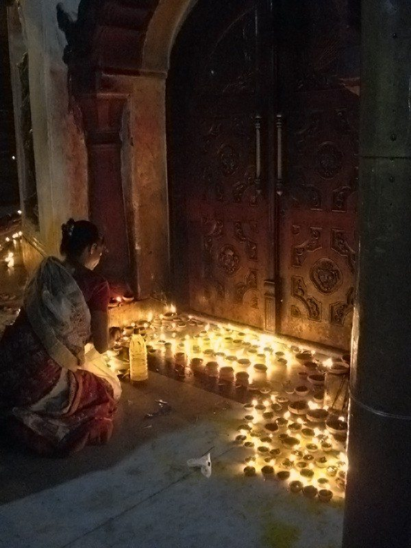 A woman lights diyas during Divali at the Sri Sri Kamakhya temple. Photo courtesy of Kulasundari Devi.